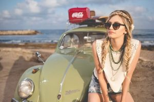 Junge Frau sitzt auf altem VW Käfer